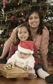 Hispanic mother and children in front of Christmas tree — Stok fotoğraf