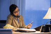 Hispanic businesswoman using telephone and cell phone — Stock Photo