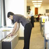 Kvinnan tittar igenom filer i office — Stockfoto