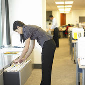 Woman looking through files in office — Stok fotoğraf