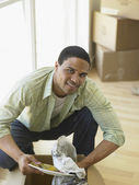 Young man unpacking dishes — Stock Photo