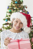 Girl pulling the ribbon off Christmas present — Stock Photo