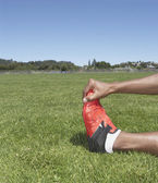 Male track athlete stretching — Stock Photo
