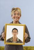 Proud mother holding picture of son — Stock Photo