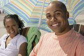 Portrait of couple sitting under umbrella at beach — Stock Photo