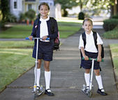 Portrait of sisters wearing uniforms on scooters — Stock Photo