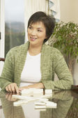 Middle-aged Asian woman playing dominoes — Stock Photo