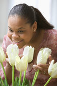 African American woman smelling tulips — Stock Photo