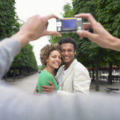 African couple having photograph taken in park — Stock Photo
