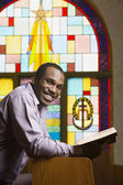 African American man with Bible in church — Stock Photo