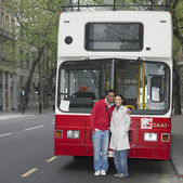 Asian couple hugging in front of tour bus in London — Stock Photo