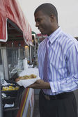 African businessman buying hot dog at outdoor stand — Stock Photo