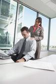 Femme d'affaires hispanique donnant hisoire homme d'affaires, un massage d'épaule dans son aire de travail — Photo