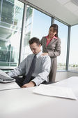 Hispanic businesswoman giving Hispanic businessman a shoulder massage in his cubicle — Stok fotoğraf