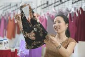 Young woman shopping for blouse — Stock Photo