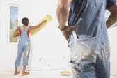 Rear view of couple painting walls — Stock Photo