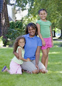 African mother with two young daughters outdoors — Stock Photo