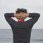 Man at the ocean with hands clasped behind head — Stock Photo