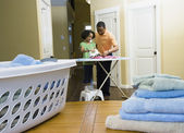 African father and daughter using iron in laundry room — Stock Photo