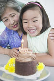 Asian girl celebrating birthday with grandmother — Stock Photo