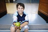 Portrait of boy on steps holding apple — Stock Photo
