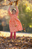 Young girl playing in pile of leaves — Stock Photo