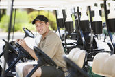 Portrait of Asian man in golf cart — Stock Photo