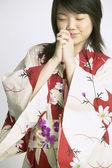 Woman in kimono praying — Stock Photo