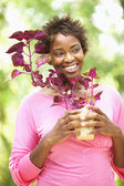 Woman holding plant and smiling — Stock Photo