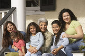 Female Hispanic family members sitting on the porch smiling — Stock Photo