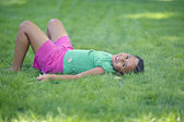 Young African girl laying in grass smiling — Stock Photo