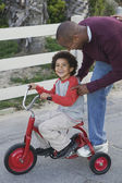African man helping son on tricycle — Stock Photo