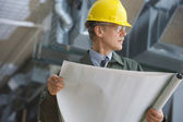 Businessman in hard hat holding blueprints — Stock Photo