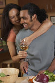 Couple hugging and drinking while cooking — Stock Photo