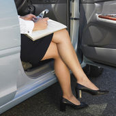 Eurasian businesswoman working in car — Stock Photo