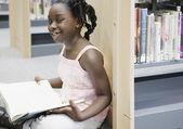 Meisje bedrijf boek in bibliotheek — Stockfoto