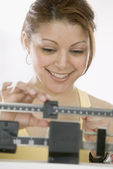 Woman weighing herself on scale — Stock Photo