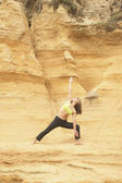Woman stretching by rock cliff — Stock Photo