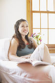 Young woman relaxing in an armchair — Stock Photo