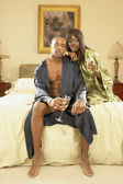 Couple in robes with champagne in bedroom — Stock Photo