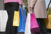 Dos mujeres con muchas bolsas de compras — Foto de Stock