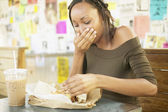 Woman eating sandwich in cafe — Stock Photo
