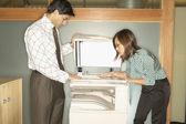 Businesspeople using copy machine — Stock Photo