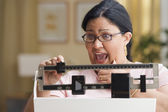 Shocked woman weighing herself — Stok fotoğraf