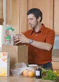 Man unpacking groceries in kitchen — Stock Photo