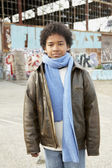 African boy wearing winter clothes in urban scene — Stock Photo