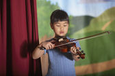 Young Asian girl playing violin at recital — ストック写真
