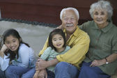 Senior couple smiling with granddaughters — Stock Photo