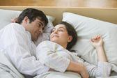 Hispanic couple smiling at each other in bed — Stock Photo