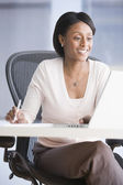 African American businesswoman looking at laptop — Stock Photo
